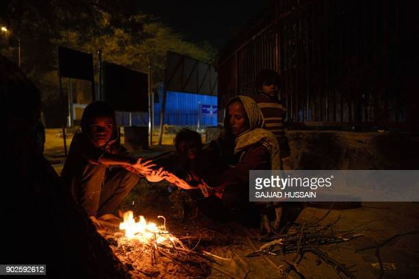 TOPSHOT An Indian family warms up around a fire along a roadside in New Delhi on January 8 2018 / AFP PHOTO / SAJJAD HUSSAIN