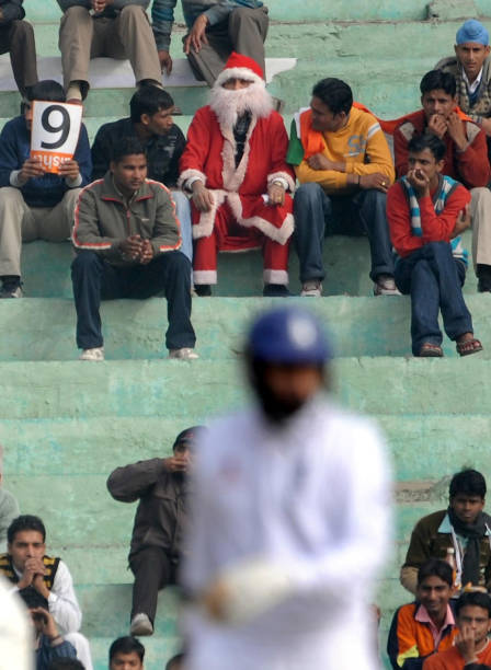 An Indian Fan Dresses As Father Christmas Englands Monty Panesar Bats During The Fourth Day