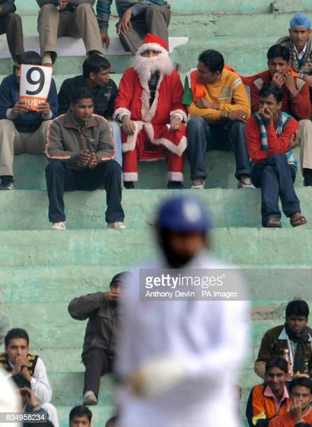 An Indian fan dresses as Father Christmas as England's Monty Panesar bats during the fourth day of the second test at the Punjab Cricket Association...