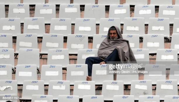 An Indian fan feels the cold during the first day of the second test at the Punjab Cricket Association Stadium Mohali India