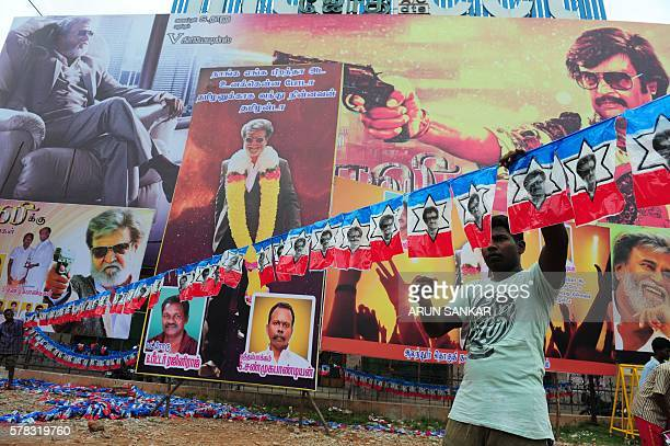 An Indian fan strings a row of flags in front of a hoarding of Indian movie star Rajinikanth erected in front of a movie theatre ahead of the release...