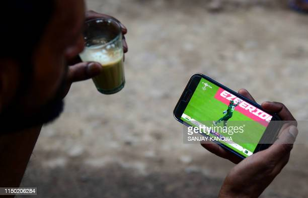 An Indian fan watches a live broadcast of the Cricket World Cup match between India and Pakistan on a mobile phone in Allahabad on June 16, 2019.