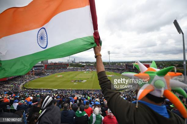 An Indian fan waves a national flag as India's openers bat under cloudy skies during the 2019 Cricket World Cup group stage match between India and...
