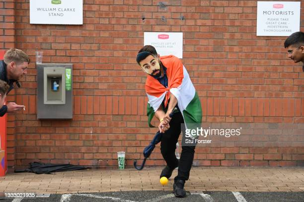 An Indian fan wearing a mask with the image of captain Virat Kohli is pictured playing cricket with an umbrella as play is delayed during day five of...