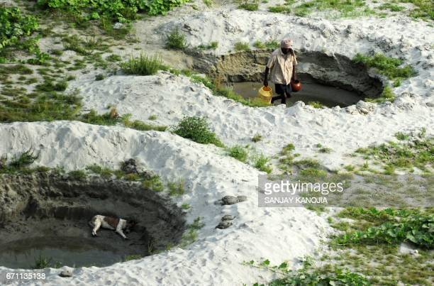 TOPSHOT An Indian farmer collects water from a temporary pond to irrigate his cucumber farm near a river bed area of the River Ganges in Allahabad on...