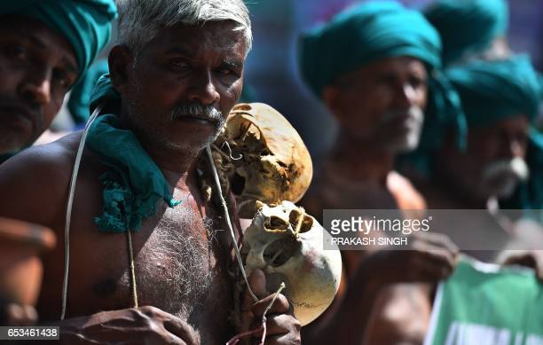 An Indian farmer from Tamil Nadu state wearing a necklace of human skulls representing suicides by agricultural workers takes part in a protest with...