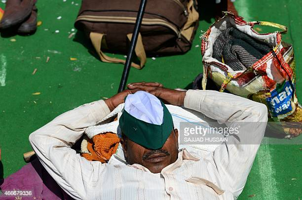 An Indian farmer naps as he takes part in a protest rally against land reforms proposed by Prime Minister Narendra Modi which they say will harm the...