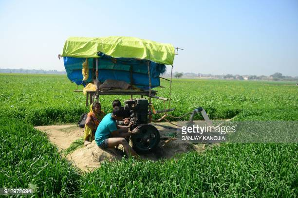 TOPSHOT An Indian farmer prepares his pumping set to irrigate his wheat field on the outskirts of Allahabad on February 1 2018 The Indian government...