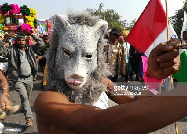 TOPSHOT An Indian farmer wearing an animal mask takes part in a march organised by the All India Kisan Sabha organization and Communist Party of...