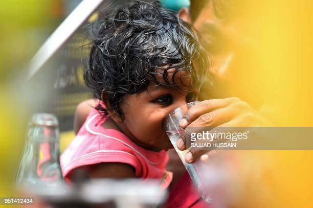 An Indian father helps his daughter to drink water on a hot summer day in the old quarters of New Delhi on April 26 2018