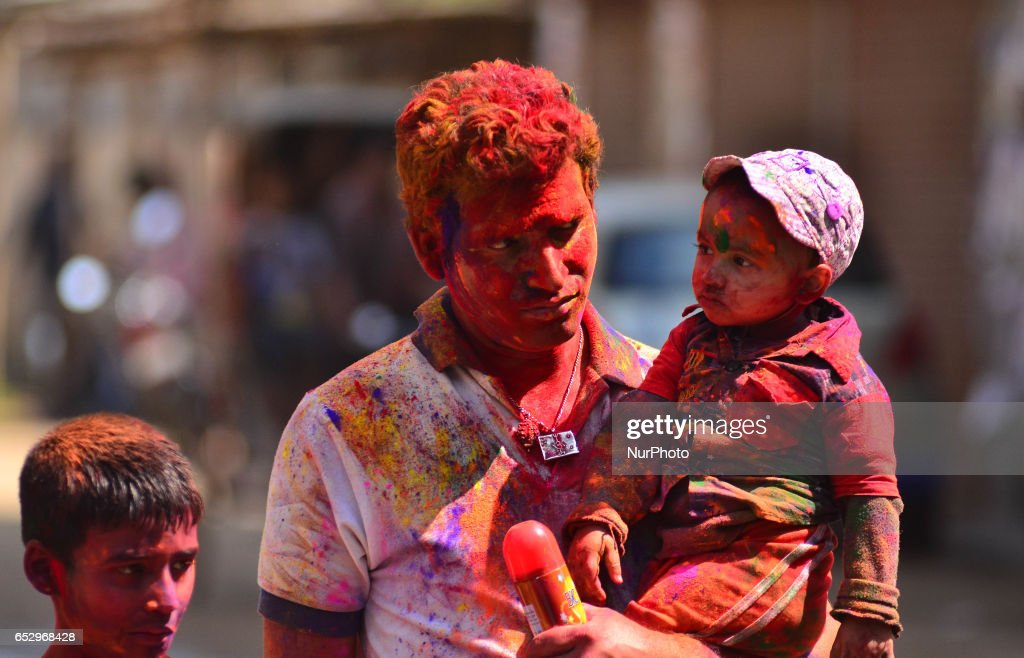 An Indian father smear with colour carries his kid during Holi celebration in Dimapur, India north eastern state of Nagaland on Monday, March 13, 2017. Holi, the festival of colours, is a riotous celebration of the coming of spring and falls on the day after full moon annually in March.