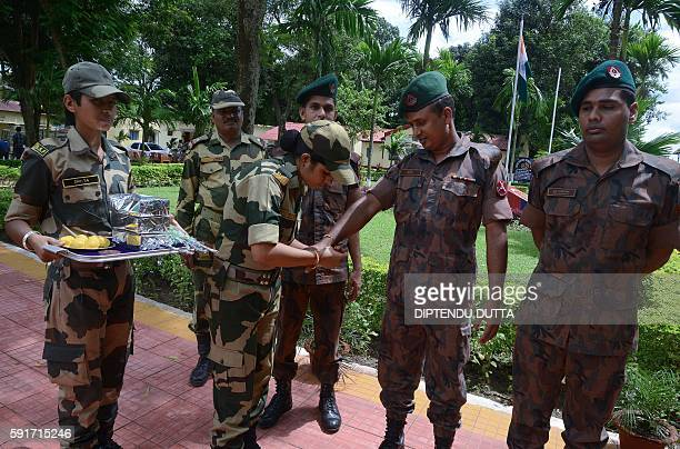 An Indian Female Border Security Force personnel ties a 'rakhi' or sacred thread onto the wrist of an Indian Border Security Force personnel on the...