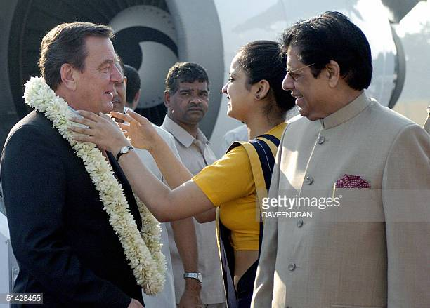 An Indian female employee from Germany's embassy in India garlands German Chancellor Gerhard Schroeder as Indian Minister of state for external...