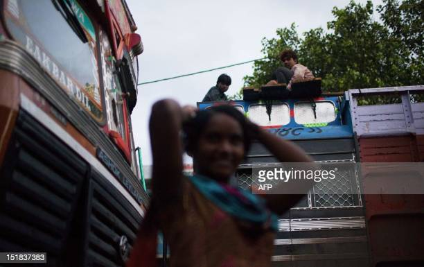 An Indian female prostitute poses as truckers resting on the top of their cab look on at the Sanjay Gandhi Transport Nagar a transport rest area in...