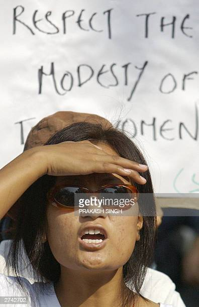 An Indian female student from the countries North-Eastern States shields her eyes from the sun as she shout slogans in front of a placard during a...