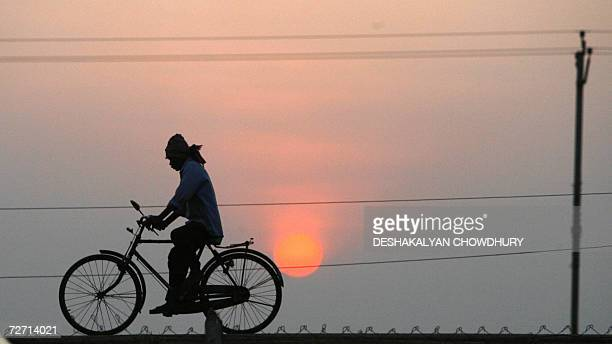 An Indian fencing worker cycles home at the end of the day's work engaged in fencing the land which is to be handed over to Indian carmaker Tata...