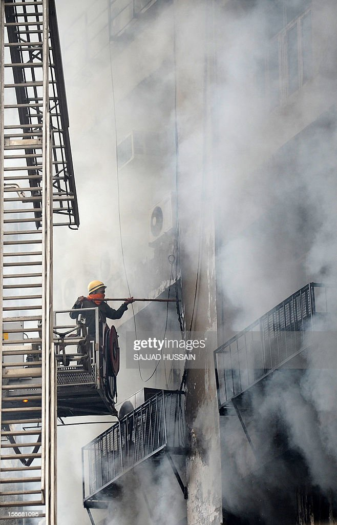 An Indian firefighter uses a stick as he investigates a fire that broke out in a fifteen story building in New Delhi early November 19, 2012. No casualities were reported in the fire.