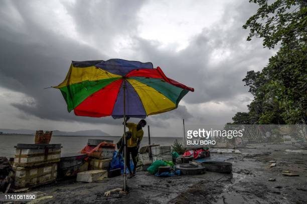 An Indian fish vendor tries to close down an umbrella as strong wind blows at a fish market on the bank of the river Brahmaputra in Guwahati on May 4...