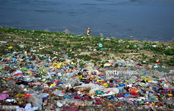 An indian fisher man walks near of A highly polluted area with plastic bags and other garbage is next to river Ganges in Allahabad India Friday Oct 2...