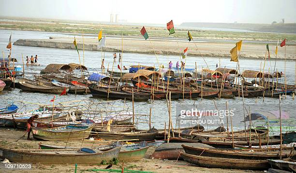 An Indian fisherman anchors his boat at Sangam the confluence of the Ganges Yamuna and Saraswati rivers in Allahabad on June 6 2010 The...