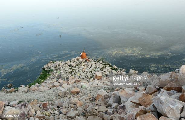 TOPSHOT An Indian fisherman catches fish in the Ganga river in Allahabad on February 23 2018 / AFP PHOTO / SANJAY KANOJIA