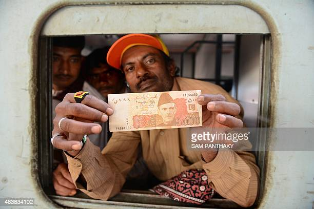 An Indian fisherman displays a 5000 Pakistani rupee note which he received from the 'Bilquis Edhi Foundation' NGO in Karachi on his arrival at the...