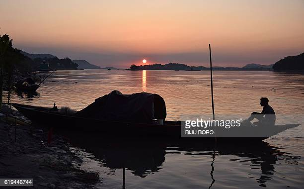 An Indian fisherman sits in his boat on the Brahmaputra River during sunset in Guwahati on October 31 2016 The Brahmaputra originates in Tibet where...