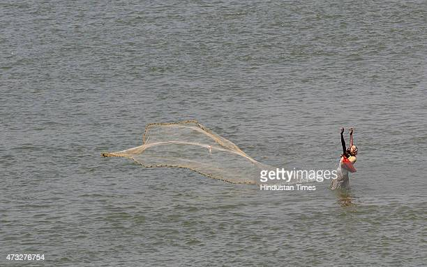 An Indian fisherman spreading his net to catch fishes in River Tawi on May 14 2015 in Jammu India