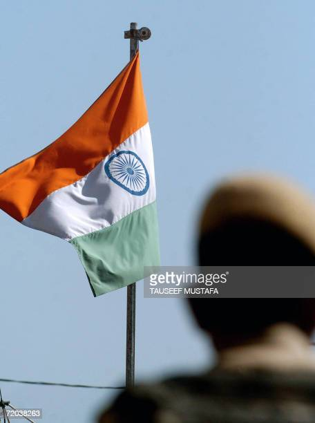 An Indian flag flies on top of a security bunker as Indian Central Reserve Police Force soldiers stand guard in front of closed shops during a strike...