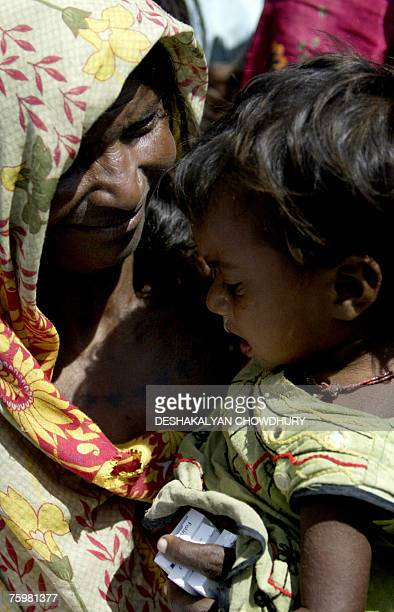 An Indian flood affected villager looks at her child as they await the attention of medical personnel in a roadside medical camp at Darbhanga some...