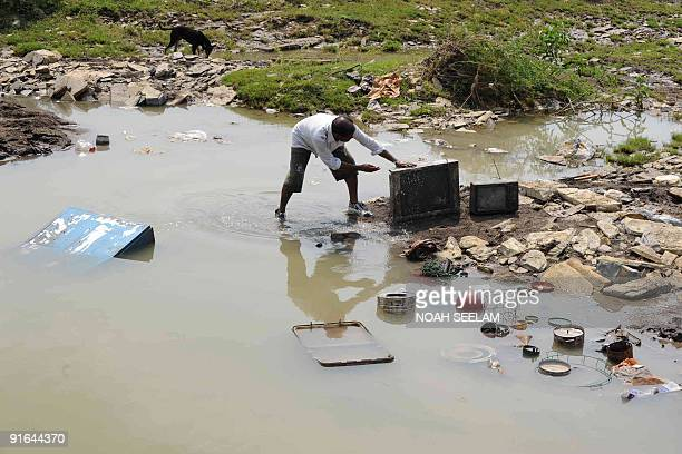An Indian flood victim cleans a televison set in the village of Allampur in Mahaboobnagar District some 240kms south of Hyderabad on October 9, 2009....
