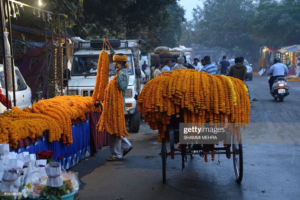 An Indian flower vendor displays garlands of marigolds for sale for Diwali rituals in Jalandhar on October 30, 2016. / AFP / SHAMMI