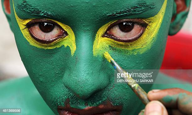 An Indian football fan has his face painted in the colours of the Brazilian flag as he prepares to cheer on Brazil's national football team in...