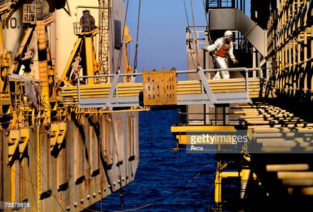 An Indian foreign 'guest worker' walks on a ramp in the technical zone of the gas and petrol separation at the Aramco offshore oil rig 'Marjan 2' in...