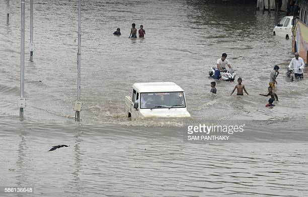 An Indian fourwheeler vehicle drives through a flooded street in Ahmedabad on August 5 2016 Heavy rains lashed many parts of western Gujarat state...