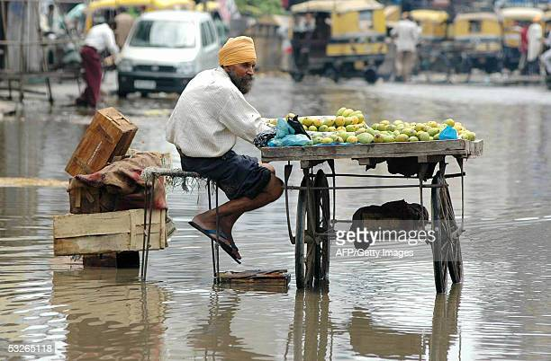 An Indian fruit vendor, Bhupinder Sethi sits on a flooded street as he waits for customers near the bus stand in Amritsar, 21 July 2005. Flooding...