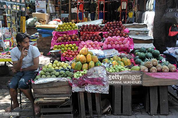 An Indian fruit vendor waits for customers at his roadside stall in Mumbai on September 20, 2011. India's benchmark wholesale price index -- the...