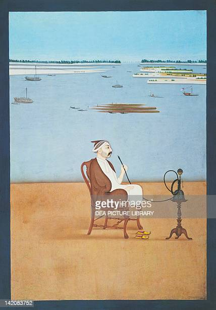 An Indian gentleman smoking a hookah whilst sitting on a Queen Annestyle chair India 18th Century