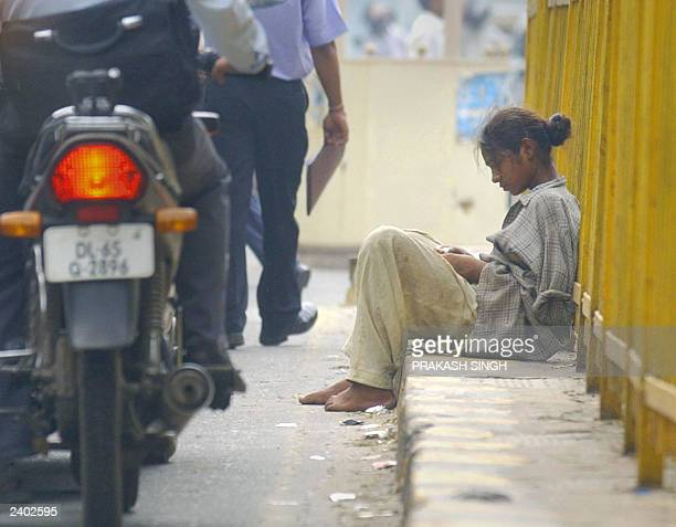 An Indian girl beggar who pretends to be handicapped whilst begging counts her days earnings at a busy traffic intersection in New Delhi 07 August...