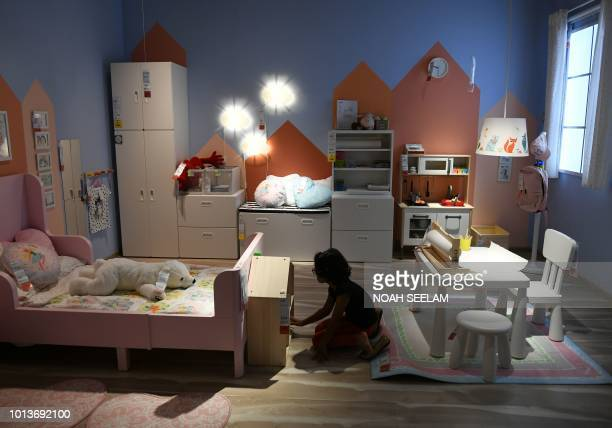 An Indian girl checks furnitures at the new IKEA store in Hyderabad on August 9 2018 Curious customers lay on beds and nestled into armchairs on...