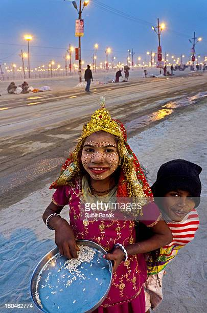 An Indian girl child, dressed as Hindu goddess with her brother on the banks of the Sangam in Allahabad on January 25, 2013. The Sangam is a holy...
