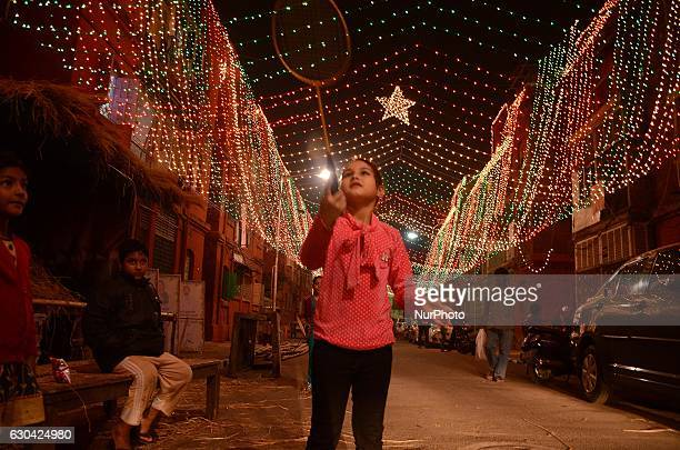 An Indian girl child playing in the streets of Bow Barracks inhibited by mainly AngloIndians and Christians decorated with lights for Christmas...