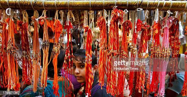 An Indian girl chooses a Rakhi at a roadside shop in Karol Bagh on the eve of Raksha Bandhan on August 19 2013 in New Delhi India The Raksha Bandhan...