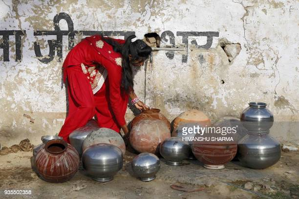 TOPSHOT An Indian girl collects drinking water from a tap in a village on the outskirts of Ajmer in the Indian state of Rajasthan on March 21 2018...