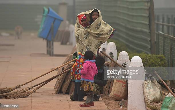 An Indian girl covers herself and a child as she stands at the roadside on a cold foggy morning in New Delhi on December 7 2016 / AFP / Money SHARMA