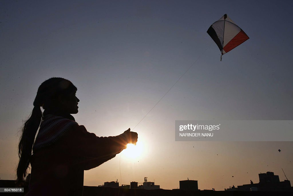 An Indian girl flies a kite during celebrations for the Lohri festival in Amritsar on January 13 2016 The Lohri harvest festival which falls on...