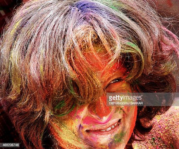An Indian girl grimaces as her friends smear her with Aabir during the celebration of the Indian traditional festival Holi in Bangalore 14 March 2006...