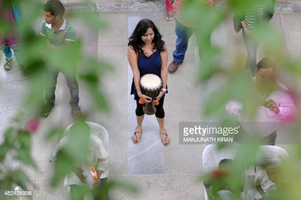 An Indian girl holding a drum watches musicians perform during the 13th Community Drumjam organised by 'DrumjamThe Worldwide DrumCircle Movement' at...