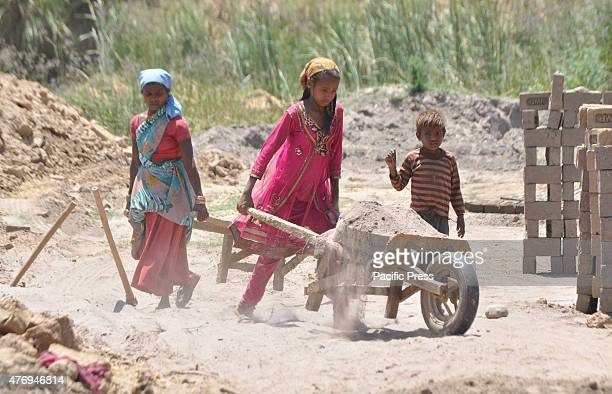An Indian girl Kavita works along with her family at a brick kiln in outskirts of Jammu on the eve of The World Day against Child Labor which is...