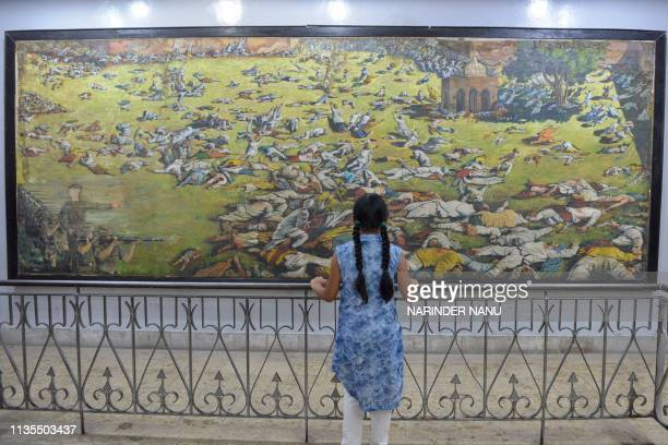 TOPSHOT An Indian girl looks at a painting of the martyrs ahead of the 100th anniversary of the Jallianwala Bagh massacre in Amritsar on April 7 2019...